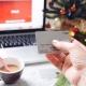 Mano de mujer con tarjeta de credito a punto de hacer compras por Internet a traves de su computadora portatil, junto con una taza de cafe y el arbolito de Navidad al fondo.